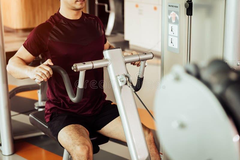 体育人正面图使用背部肌肉舒展机器的叫在健身健身房的供以座位的行 人生活方式和体育锻炼 图库摄影