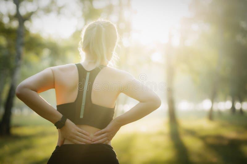 体育伤害 充满背部疼痛的妇女 库存照片