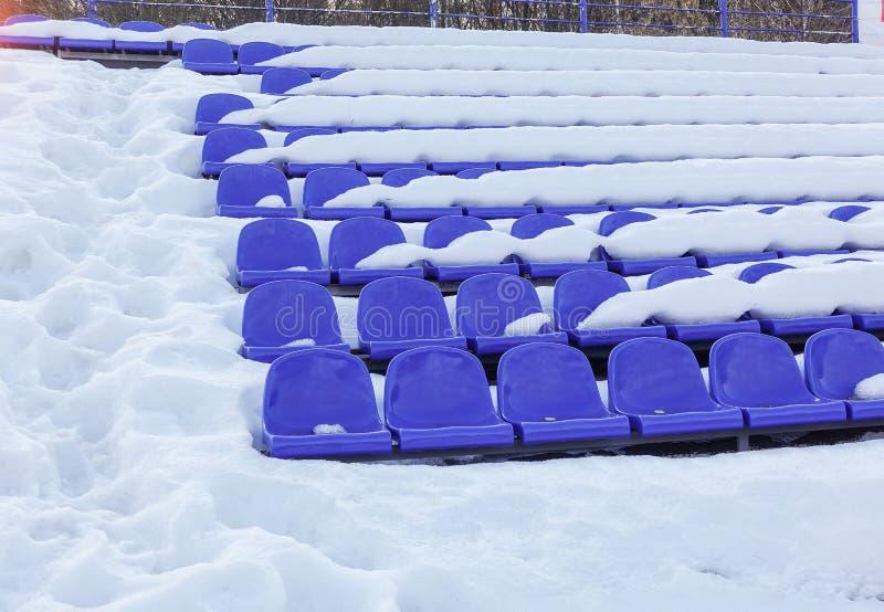 体育体育场漂白剂在冬天,爱好者的椅子-雪盖的正面看台空位进去  库存图片