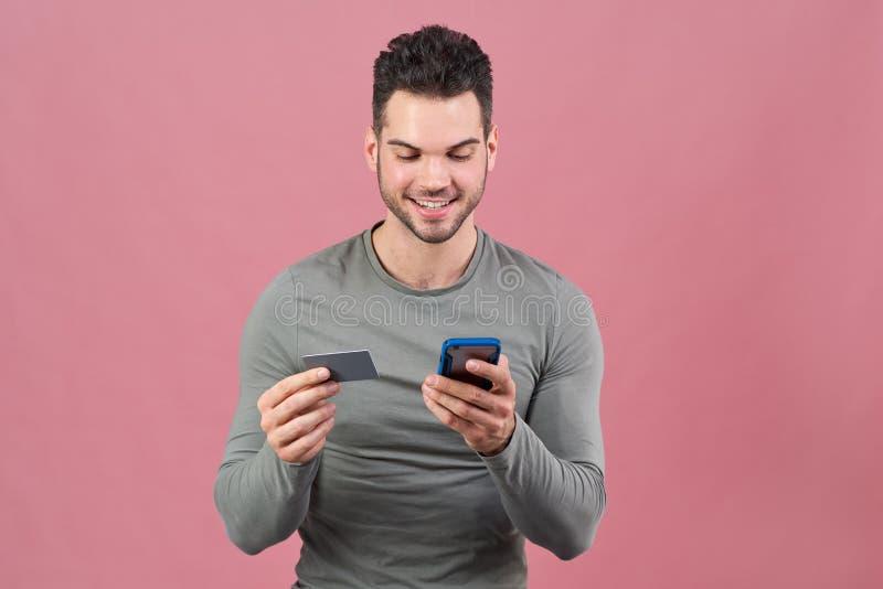 体育体质的一个年轻友好的人拿着一个智能手机和一个银行卡在他的手上 正面情感,在她的面孔的微笑 免版税库存照片
