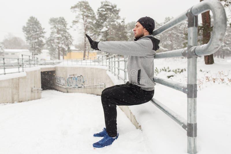 体育供以人员做蹲坐在篱芭在冬天 图库摄影
