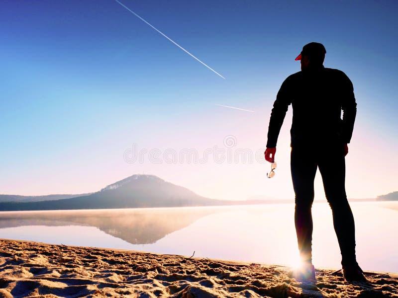 体育供以人员停留在与在手中玻璃的华美的日落海滩和享受日落 免版税图库摄影