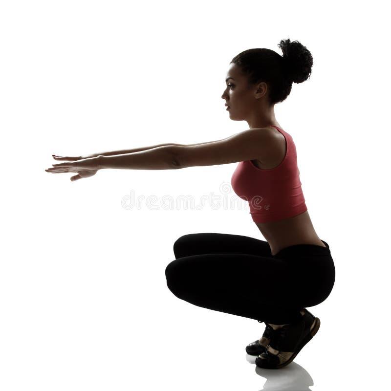体育做蹲锻炼,活跃fitne的年轻女人运动员 免版税库存图片