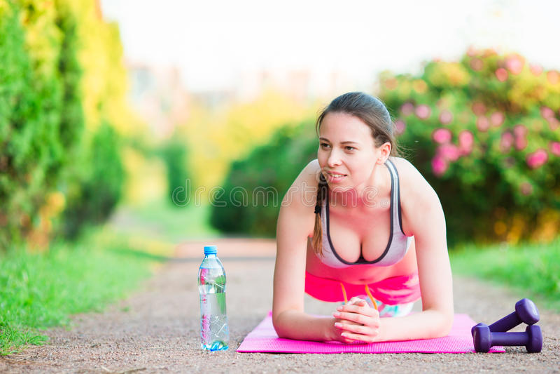 体育健身女孩训练俯卧撑 女运动员行使在空的公园增加外面 概念健康生活方式 免版税图库摄影