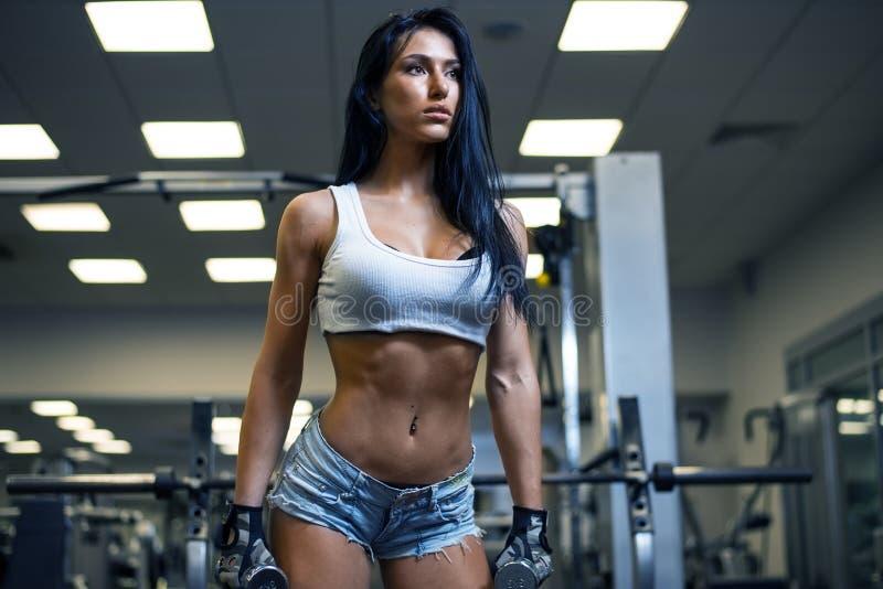 体育健身房的年轻性感的女孩 免版税库存照片