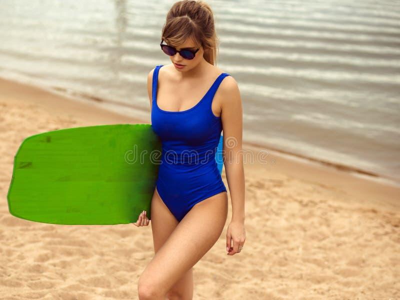 体育别致的样式的年轻白肤金发的妇女与在海滩的冲浪板 免版税库存图片