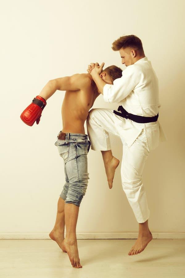 体育和作战,空手道运动员跳跃,踢膝盖在拳击手 免版税图库摄影