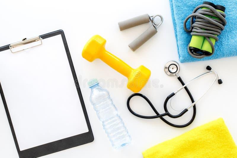 体育和健康 健身 哑铃和听诊器在白色背景顶视图大模型 免版税库存照片