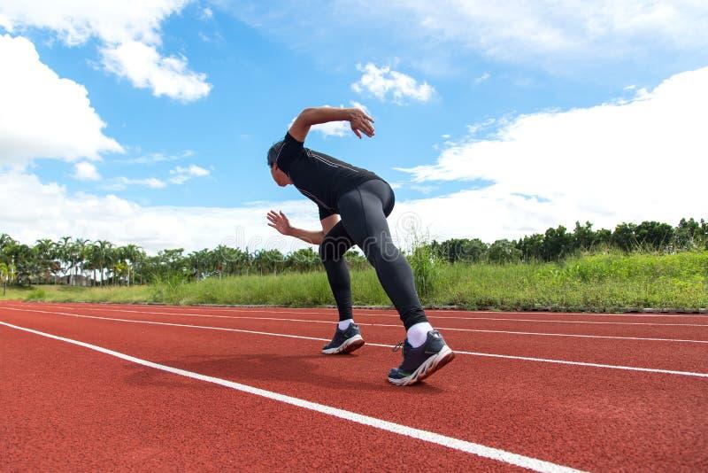 体育和健身赛跑者供以人员在跑马场训练的赛跑 免版税库存照片