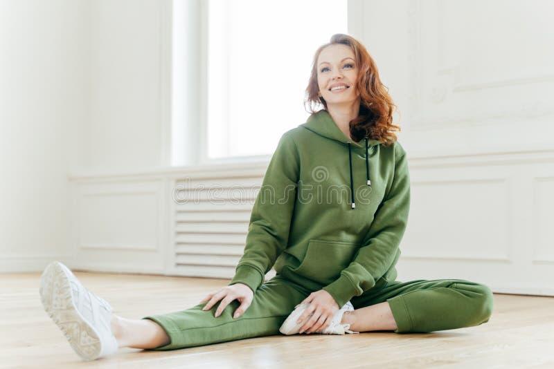体育和刺激概念 适合的微小的运动服的,舒展腿姜白种人女性,有早晨身体锻炼,聚焦了 免版税库存照片