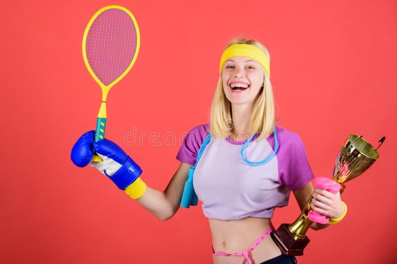 体育商店分类 女孩快乐的成功的现代妇女举行金黄觚体育冠军和设备红色 免版税库存照片