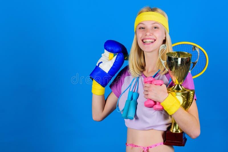 体育商店分类 女孩成功的现代妇女举行金黄觚体育冠军和设备蓝色背景 免版税库存图片