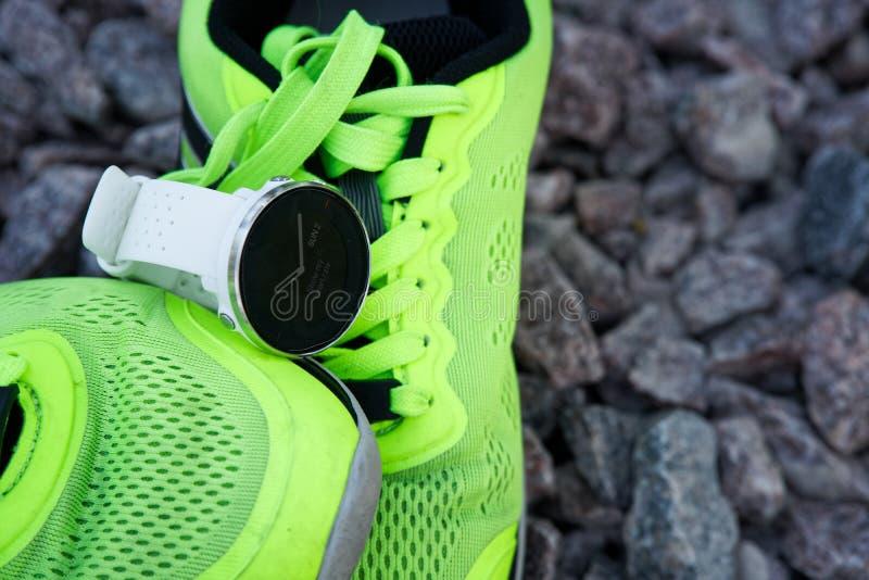 体育在绿色跑鞋的注意crossfit和三项全能 巧妙的注意跟踪的每日活动和力量训练 库存照片