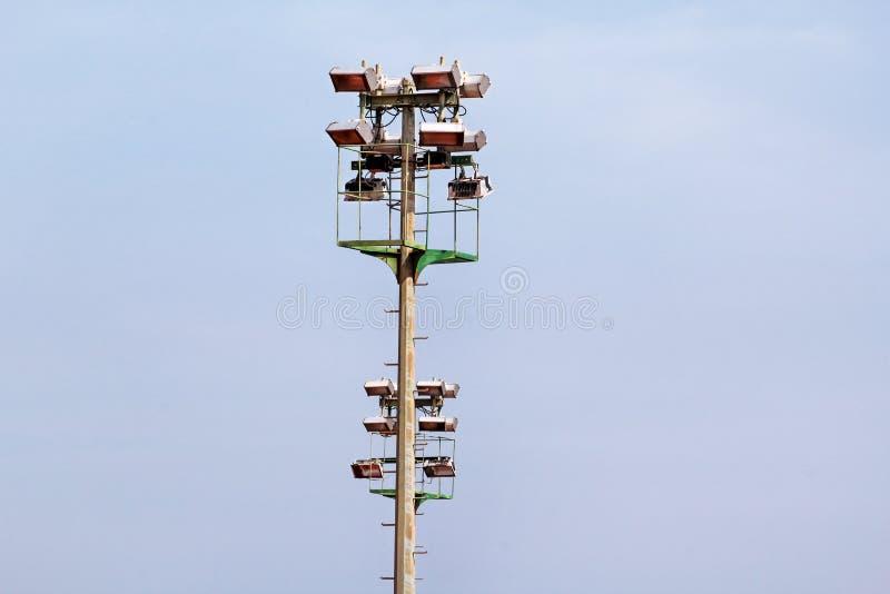 体育场与反射器的泛光灯塔有蓝天backgroun的 库存照片