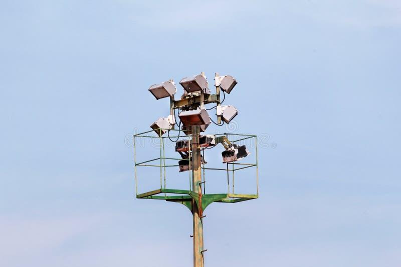 体育场与反射器的泛光灯塔有蓝天backgroun的 库存图片