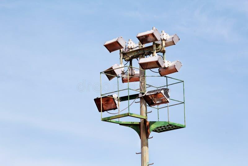 体育场与反射器的泛光灯塔有蓝天backgroun的 免版税库存照片