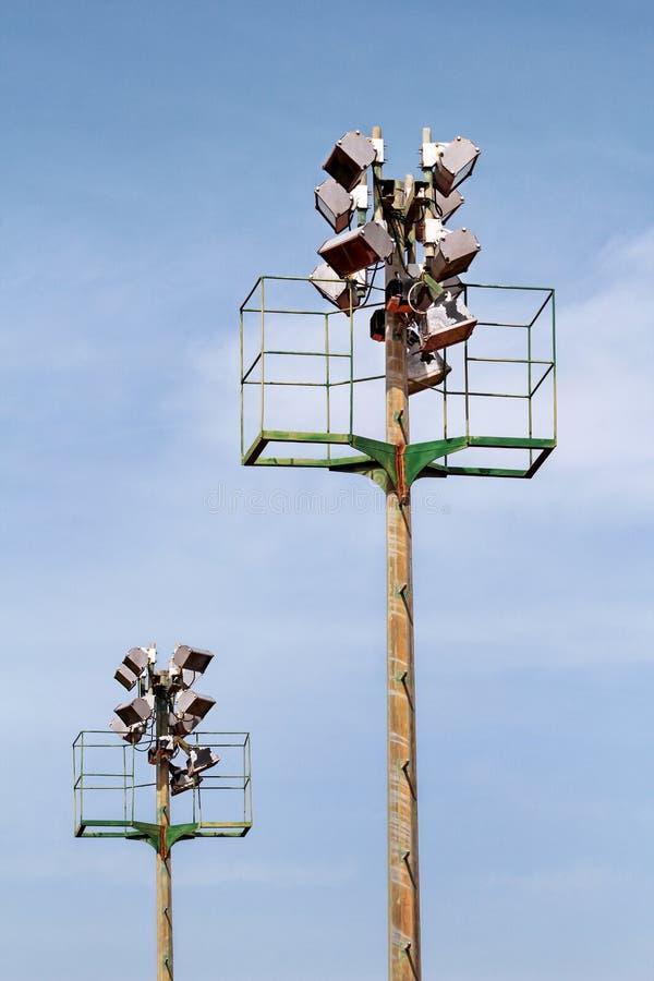 体育场与反射器的泛光灯塔有蓝天backgroun的 免版税库存图片