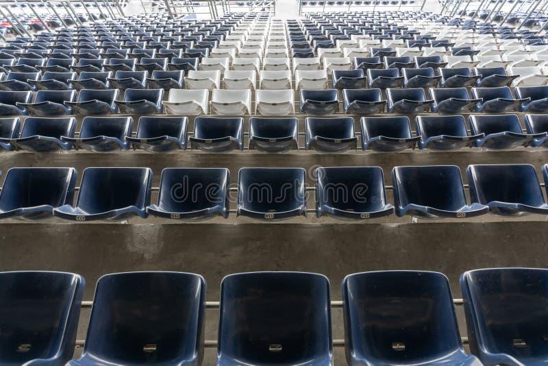体育场正面看台位子或体育场位子,塑料蓝色和白色位子空的行在盛大体育场样式 免版税库存图片
