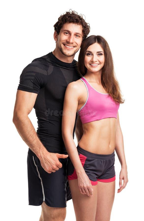 体育夫妇-男人和妇女在健身以后在白色行使 免版税库存图片
