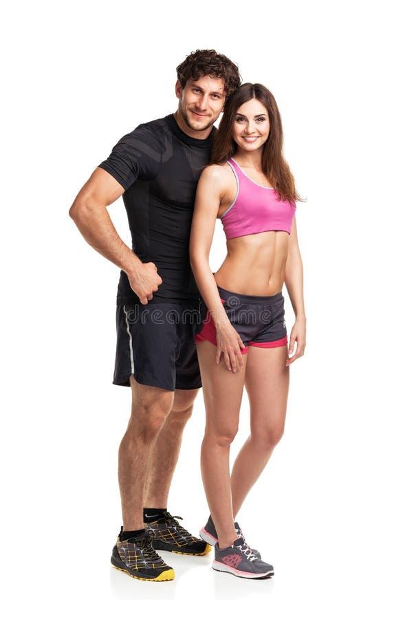 体育夫妇-男人和妇女在健身以后在白色行使 免版税库存照片