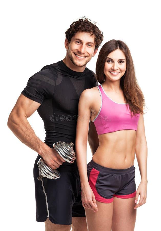 体育夫妇-男人和妇女有哑铃的在白色 免版税库存图片
