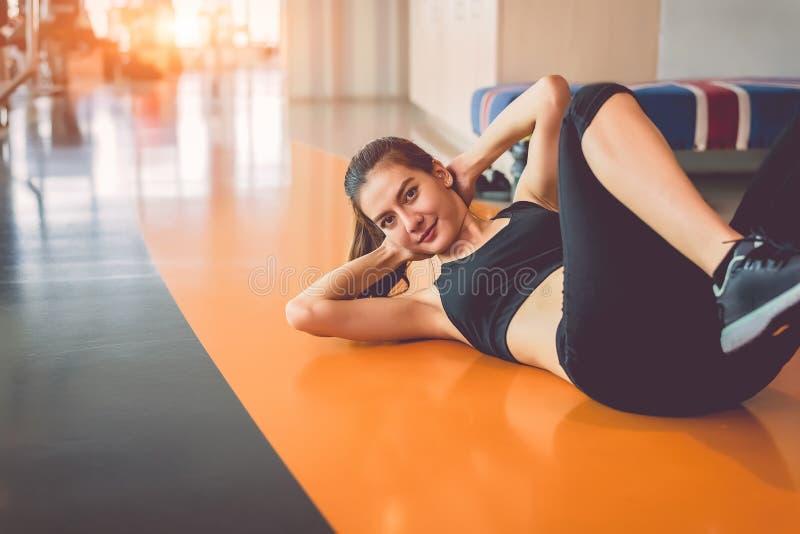 体育妇女做在健身体育训练俱乐部坐直用运动器材和辅助部件背景 锻炼咬嚼和 免版税库存图片