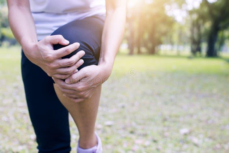 体育妇女安排膝盖痛苦或腿伤以后解决在公园 库存图片