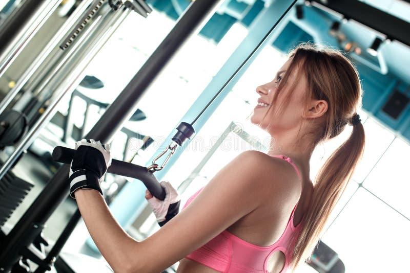 体育手套的少女在健身房健康生活方式行使在缆绳机器藏品酒吧的看在旁边快乐  库存照片