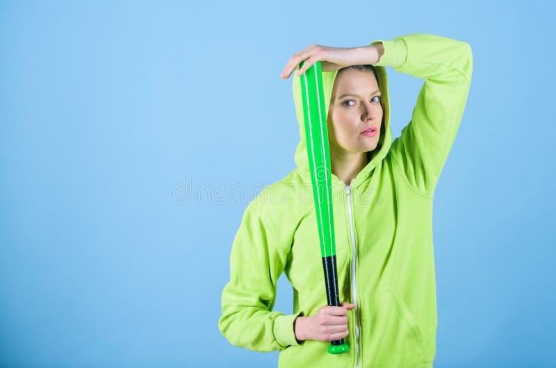 体育比赛 妇女戏剧棒球或去打某人 女孩戴头巾夹克举行棒球棒蓝色背景 库存照片