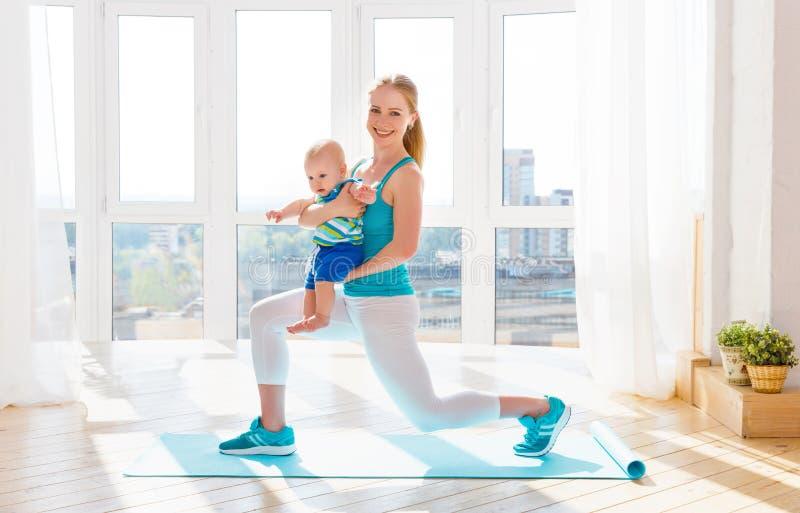 体育照顾在家参与健身和瑜伽与婴孩 免版税库存照片