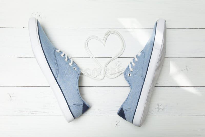体育牛仔布运动鞋、心脏和恋人概念 免版税库存照片