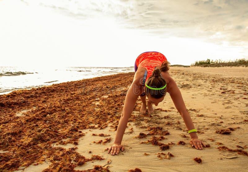 体育的年轻活跃妇女在海岸舒展适应 免版税库存图片