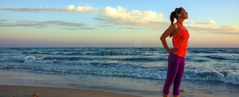 体育的轻松的少妇在海岸适应在日落 免版税库存照片