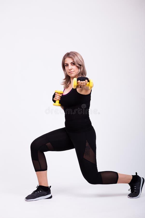 体育的适合的妇女给行使与两个小哑铃穿衣 免版税图库摄影