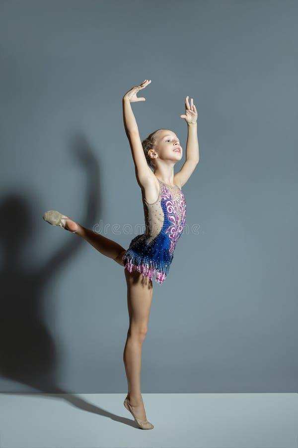 体育礼服的美女体操运动员执行一锻炼,艺术性的元素 灰色背景 库存图片