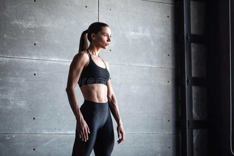 体育穿在黑暗的墙壁背景的妇女画象黑运动服 库存照片