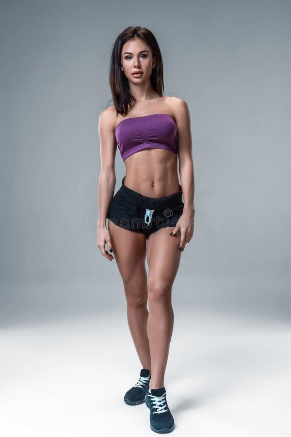体育穿戴的深色的性感的健身女孩与完善的身体在摆在训练的演播室集合前 大赃物 免版税图库摄影