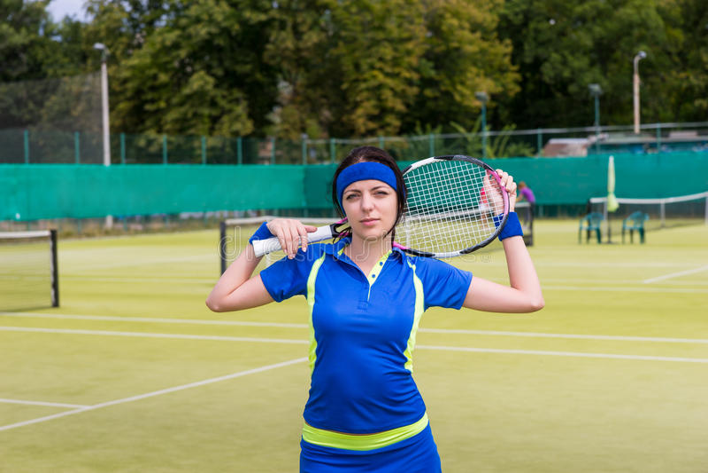 体育穿戴的年轻attracive妇女保留在她的网球拍 免版税库存照片