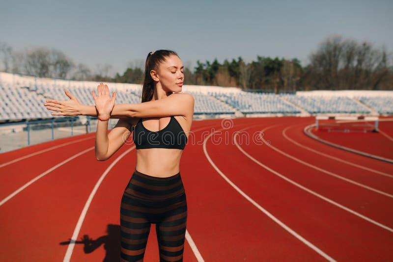 体育舒展在体育场的健身妇女 在有许多轨道的体育连续竞技场炫耀舒展胳膊的白肤金发的女孩 免版税库存图片