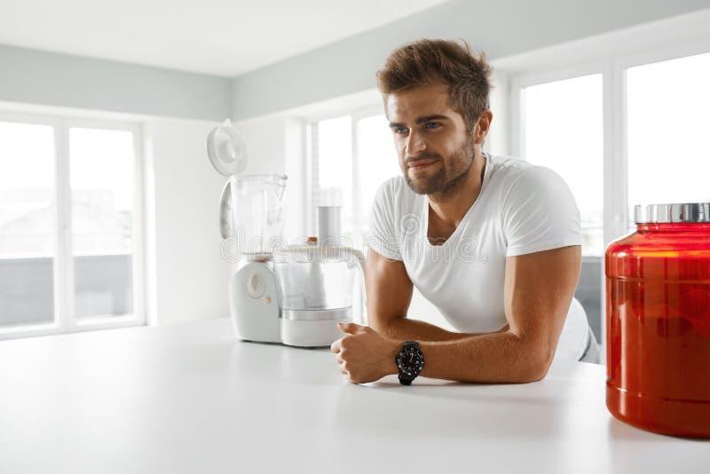 体育营养 去健康的人准备震动在厨房里 免版税库存图片