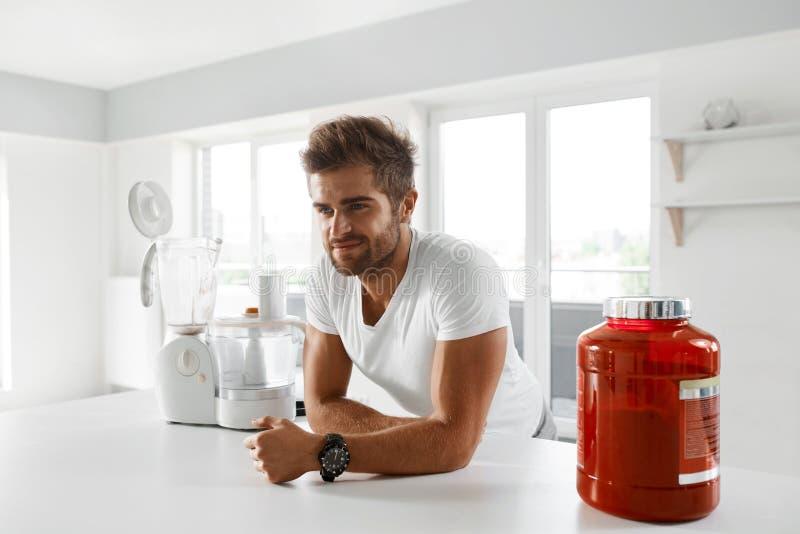 体育营养 去健康的人准备震动在厨房里 免版税库存照片