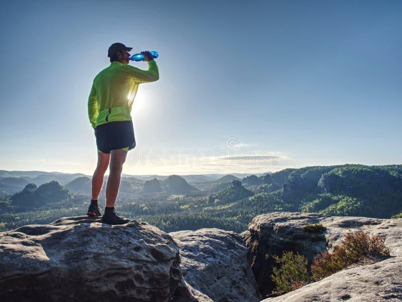 体育衣服的适合赛跑者喝从体育瓶的水 库存图片