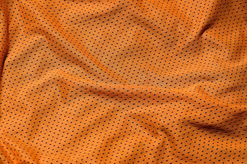 体育衣物织品纹理背景 橙色聚酯尼龙布料纺织品表面顶视图  色的篮球衬衣与 免版税库存照片