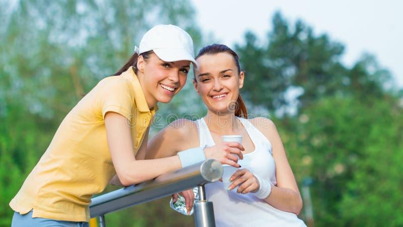 体育衣物饮用水的快乐的女朋友 免版税库存照片