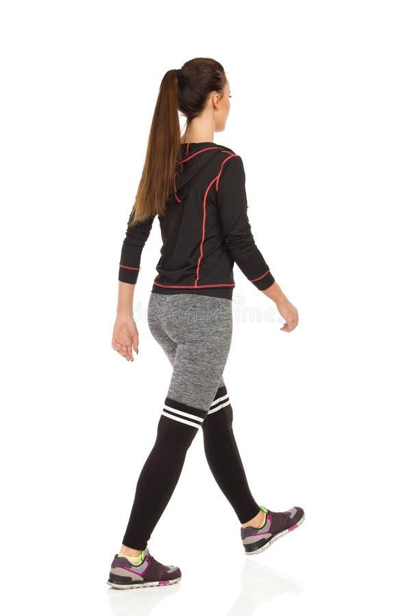 体育衣裳的少妇走 后面视图 免版税库存图片