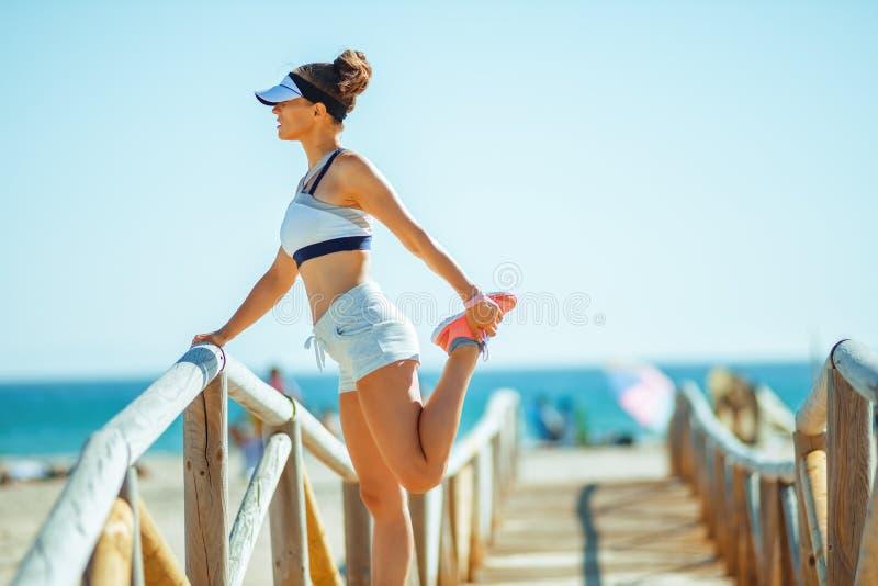 体育衣裳的年轻体育妇女在海洋海岸舒展 免版税库存照片