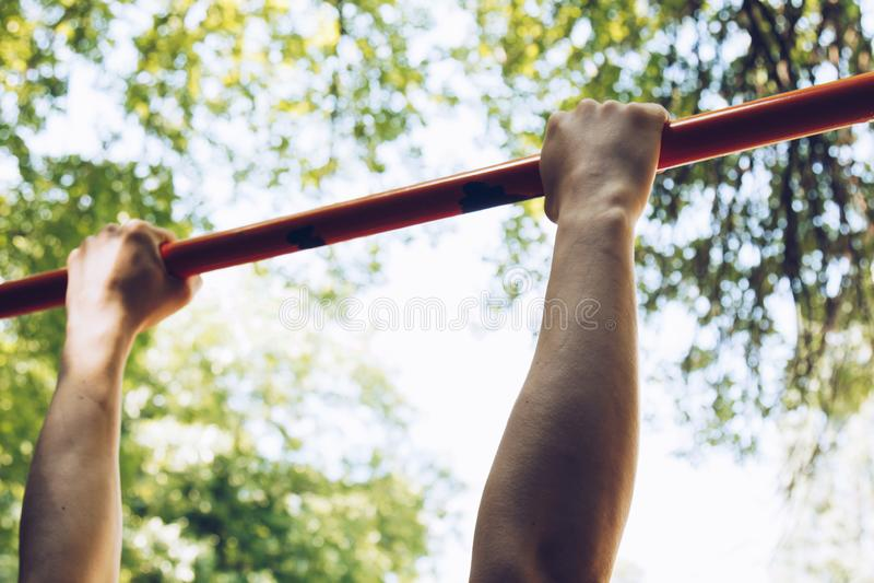 体育运动员的手坚持引体向上的一条金属标志横线在训练场反对清楚的天空和绿色 免版税库存照片