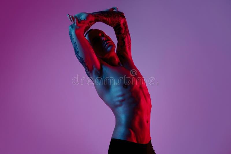 体育适合可爱的人时尚photoshoot做胳膊的舒展 男性赤裸身体,被刺字的手,行家神色 颜色闪光 免版税库存照片