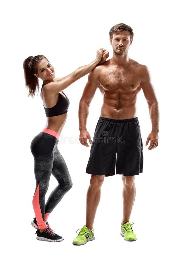 体育,健身,锻炼概念 适合的夫妇、坚强的肌肉摆在白色背景的男人和亭亭玉立的妇女 免版税库存图片