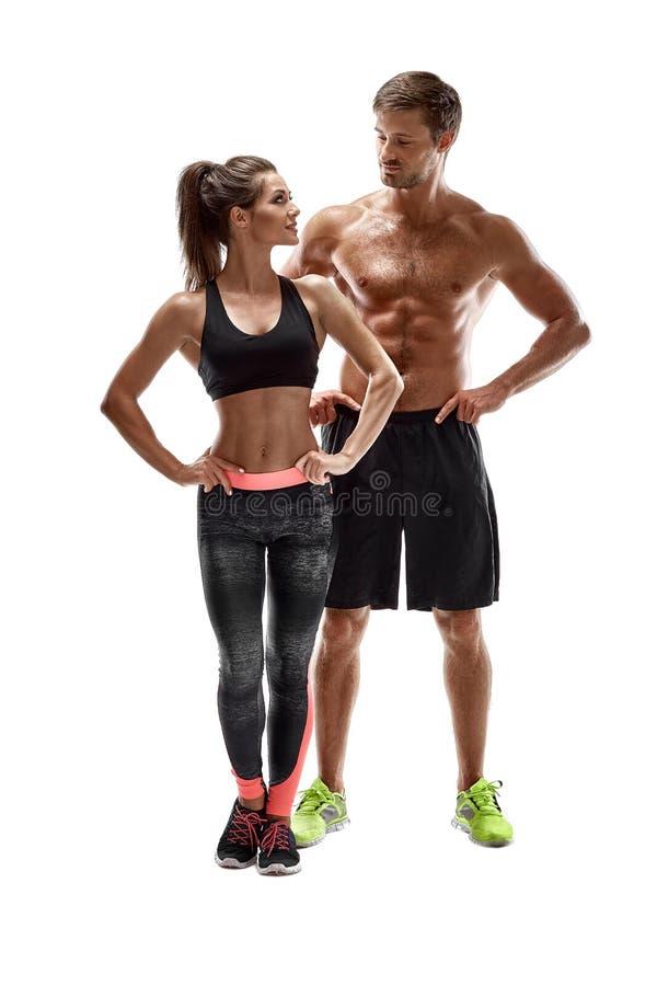 体育,健身,锻炼概念 适合的夫妇、坚强的肌肉摆在白色背景的男人和亭亭玉立的妇女 免版税图库摄影
